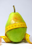 Diet and exercise. Fresh appetizing pear with a measuring tape. focus on the pear royalty free stock photography