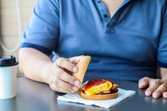 Diet failure of fat man eating fast food hamberger. Happy smile overweight person . Hate to diets. Very fat man eating fast food, royalty free stock photography