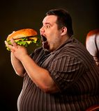Fat man eating fast food hamberger. Breakfast for overweight person. royalty free stock photography