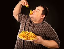 Fat man eating fast food french fries for overweight person. Diet failure of fat man eating fast food. Overweight person who spoiled healthy food by eating Royalty Free Stock Photo