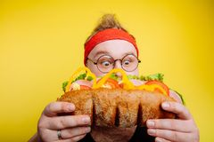 Diet failure of fat man eating fastfood. Joyful fat man is smelling sandwich and smiling Stock Images