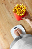 Diet, Fast Food. Woman On Scale, French Fries. Obesity. Royalty Free Stock Images