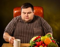 Diet fat man eating healthy food . Healthy slimming tea. Diet fat man drinking slimming green tea, eating healthy food with vegetables for overweight person stock photography