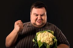 Diet fat man eating healthy food . Low quality meal product. Diet fat man eating healthy food . Healthy breakfast with vegetables cauliflower for overweight royalty free stock photo