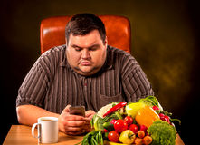 Diet fat man eating healthy food and orders by phone . Diet fat man eating healthy food . Healthy breakfast with vegetables for overweight person. Male trying stock images