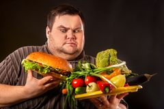 Diet fat man makes choice between healthy and unhealthy food. stock photos