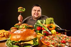 Diet fat man makes choice between healthy and unhealthy food. royalty free stock photography