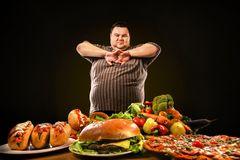 Diet fat man makes choice between healthy and unhealthy food. royalty free stock image