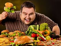Diet fat man makes choice between healthy and unhealthy food. stock photo