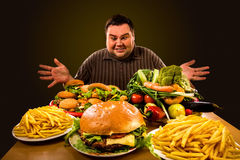 Diet fat man makes choice between healthy and unhealthy food. Stock Images