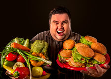 Diet fat man makes choice between healthy and unhealthy food. royalty free stock photos