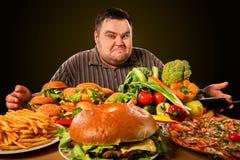 Diet fat man makes choice between healthy and unhealthy food. Diet fat man who makes choice between healthy and unhealthy food . Overweight male with hamburgers stock photos