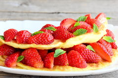 Diet filled omelette. Colorful omelette filled with fresh strawberries and garnished with mint on a plate and old wooden table Stock Photos