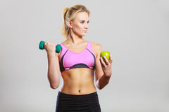 Diet fit body. Girl holds dumbbells and apple fruit Stock Photos