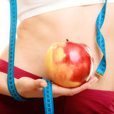 Diet. Fit girl with measure tape and apple fruit Stock Image