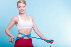 Diet. fit girl with measure tape measuring waist Royalty Free Stock Photo