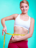 Diet. fit girl with measure tape measuring waist Stock Photos
