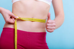 Diet. fit girl with measure tape measuring waist Royalty Free Stock Images