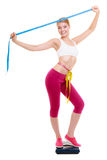 Diet. Fit girl with measure tape on weight scale Royalty Free Stock Image
