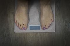 Diet and fitness concept. Close up to female bare feet with pedicure standing on scales with empty display. Woman standing on royalty free stock photos