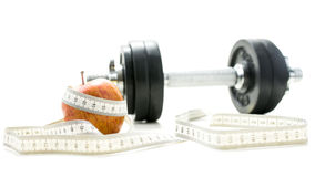 Diet and fitness concept. Weights, apple and measuring tape over white background. Dieting and fitness concept Stock Photo