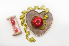 Diet and Fitness Healthy Food Regime:Glass Clock and Red ripe Apple in Heart Shape Wooden Box, tied with Cyan Measuring Tape, isol. Diet and Fitness Healthy Food Royalty Free Stock Image