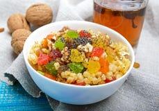 Diet fitness wheat porridge with nuts, raisins, slices of citrus fruit grapefruit, orange, kiwi, poppy seeds,. Honey, in a white bowl on a blue wooden Royalty Free Stock Image