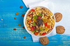 Diet fitness wheat porridge with nuts, raisins, slices of citrus fruit grapefruit, orange, kiwi, poppy seeds, honey, in a white. Bowl on a blue wooden Stock Images