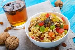 Diet fitness wheat porridge with nuts, raisins, slices of citrus fruit grapefruit, orange, kiwi, poppy seeds, honey, in a white. Bowl on a blue wooden Stock Photography