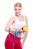Diet. Fitness woman fit girl with measure tape and apple fruit. Time for diet slimming weight loss. Health care and healthy nutrition. Young fitness woman fit Stock Photography