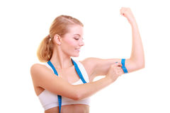 Diet. Fitness woman fit girl with measure tape measuring her biceps. Power and energy. Health care and healthy active lifestyle. Young fitness woman fit girl stock image