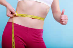 Diet. Fitness woman fit girl with measure tape measuring her waist. Time for diet slimming weight loss. Health care and healthy nutrition. Young fitness woman Royalty Free Stock Photography
