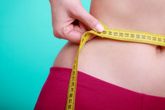 Diet. Fitness woman fit girl with measure tape measuring her waist Royalty Free Stock Photos