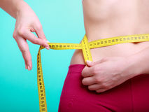 Diet. Fitness woman fit girl with measure tape measuring her waist Royalty Free Stock Image