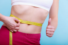 Diet. Fitness woman fit girl with measure tape measuring her waist. Time for diet slimming weight loss. Health care and healthy nutrition. Young fitness woman Stock Photography