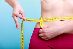Diet. Fitness woman fit girl with measure tape measuring her waist Royalty Free Stock Photography