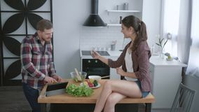 Diet food, happy guy prepares healthy vegetarian eating on brunch and girl sitting on kitchen table with mobile phone in. Hands and takes photo at cuisine stock video footage
