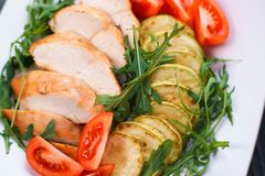 Diet food, proteins, healthy low-calorie meals concept. Baked ch. Icken breasts with zucchini, tomatoes and arugula, close up Royalty Free Stock Photography