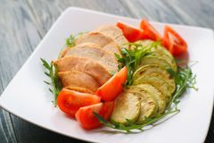 Diet food, proteins, healthy low-calorie meals concept. Baked ch. Icken breasts with zucchini, tomatoes and arugula on white plate, close up Royalty Free Stock Images