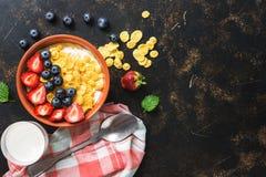 Diet-frukosten med cornflakes, mjölkar och bär på en mörk lantlig bakgrund äta för begrepp som är sunt Bästa sikt, kopieringsbrun royaltyfri bild