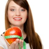 Diet. Girl holding apple with measure tape. Diet and nutrition. Happy young woman holding apple fruit with measure tape isolated on white. Girl recommending Stock Image