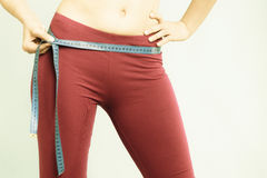 Diet. Girl with measure tape measuring loins Royalty Free Stock Photos