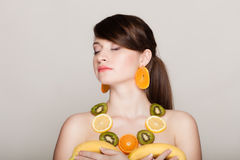 Diet. Girl with necklace of fresh citrus fruits Royalty Free Stock Image