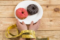 Diet. hands of a centimeter. sweet Donuts royalty free stock photo