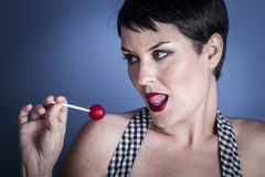Diet, happy young woman with lollypop  in her mouth on blue back Royalty Free Stock Photography
