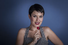 Diet, happy young woman with lollypop  in her mouth on blue back Stock Photography
