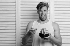 Diet and health concept. Man with disgusted face expression on background of beige jalousie. Guy in sleeveless shirt eating tape for measuring. Athlete with stock image
