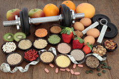 Diet Health Food and Training Regime. Body building dumbbells and hand grippers with health and super food selection including supplement powders  and fresh Royalty Free Stock Photography