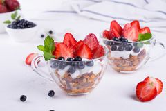 Diet healthy dessert with yogurt, granola and fresh berries. On white table background royalty free stock photography