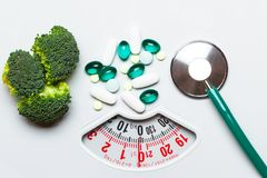 Broccoli stethoscope pills on weight scale. Dieting Royalty Free Stock Photo